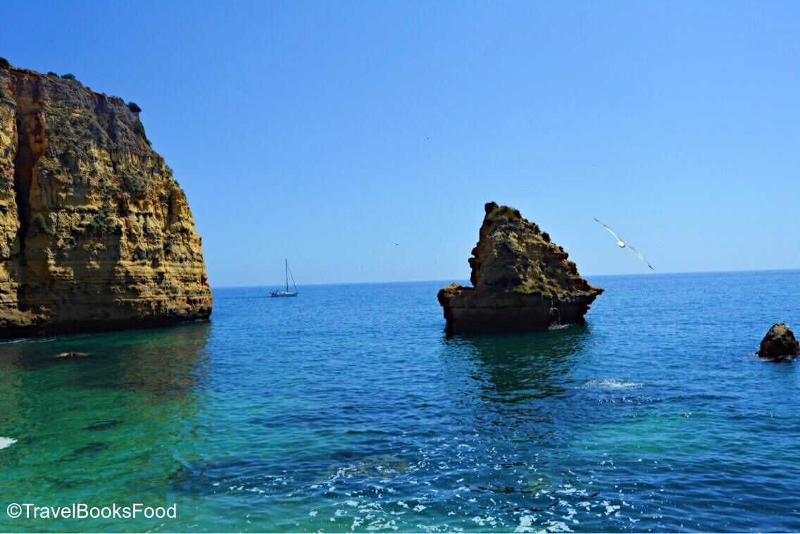 A golden cliff surrounded by turquoise waters in Algarve, Portugal
