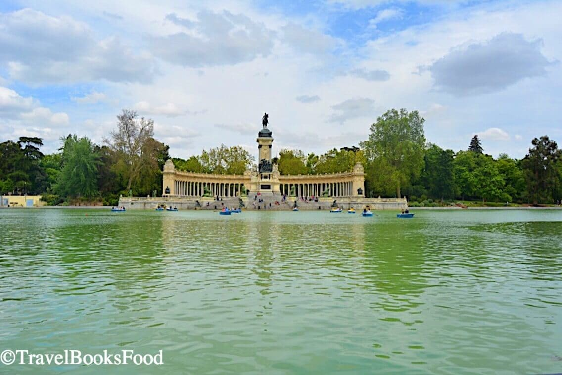 This is a photo of a monument inside the Buen Retiro Park in Madrid with a green water body in front of it.